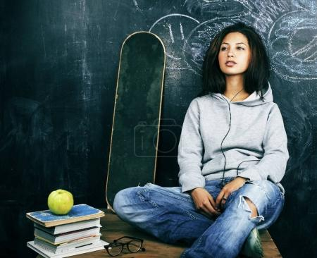 young cute teenage girl in classroom at blackboard seating on ta