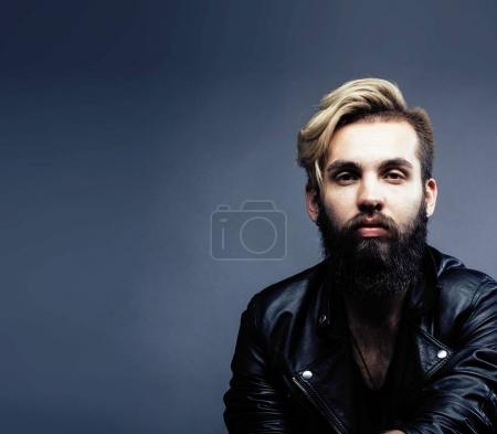 portrait of young bearded hipster guy on gray dark background cl