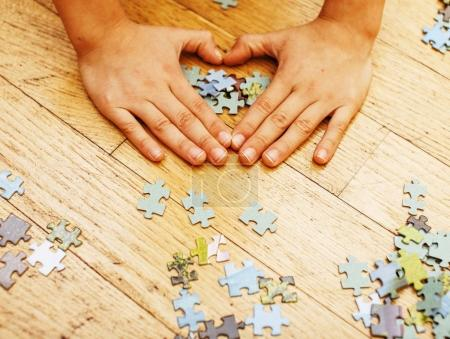 little kid playing with puzzles on wooden floor together with pa