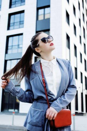 young pretty brunette business woman posing against modern build