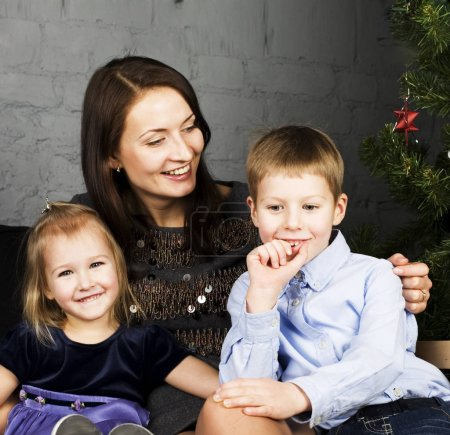 young mother with two children on gray background, happy smiling