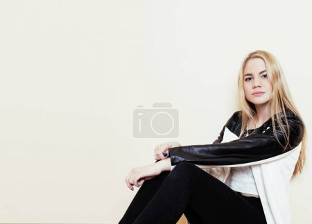 young pretty teenage blond girl sitting on floor at home despair