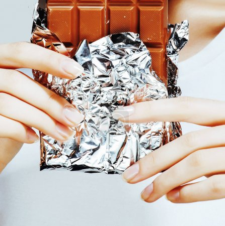 woman eating chocolate, close up hands with manicure french nails holding candy, beautiful fingers, lifestyle people concept