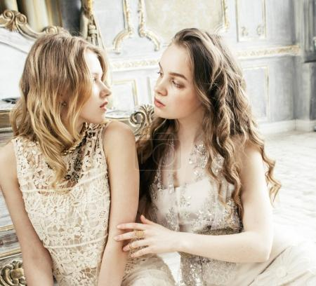 two pretty twin sister blond curly hairstyle girls in luxury house interior together, rich young people concept close up