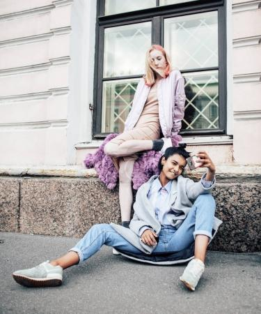 Two teenage girls infront of university building smiling, having