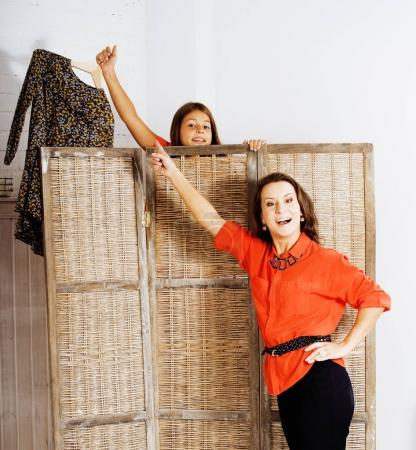 happy mother with daughter trying on dresses at home interior, h