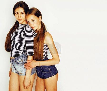 Photo pour Deux adolescents mignons s'amusent ensemble isolé sur blanc, filles amis - image libre de droit