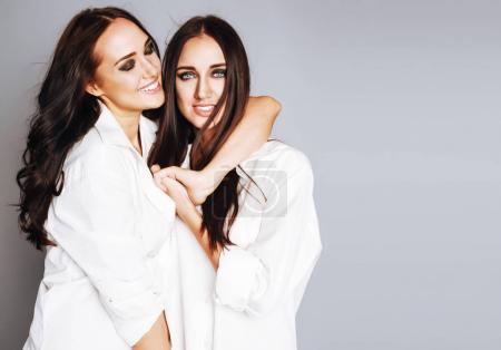 two sisters twins girl posing, making photo selfie, dressed same