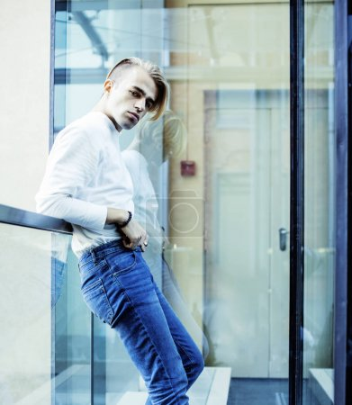 young modern hipster guy at new building university blond fashion hairstyle having fun, lifestyle people concept