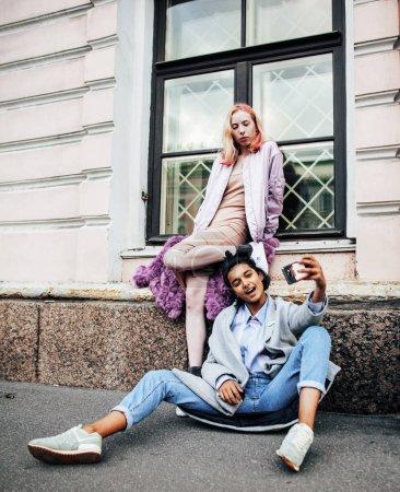 Two teenage girls infront of university building smiling, having