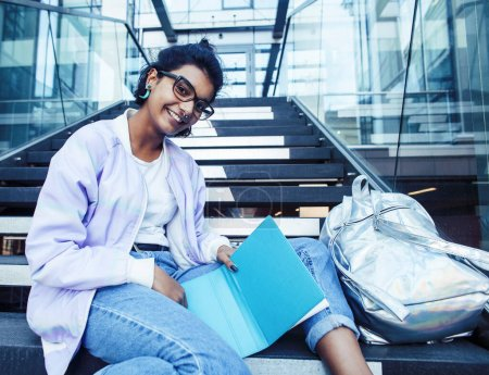 Photo for Young cute indian girl at university building sitting on stairs reading a book, wearing hipster glasses, lifestyle people concept close up - Royalty Free Image