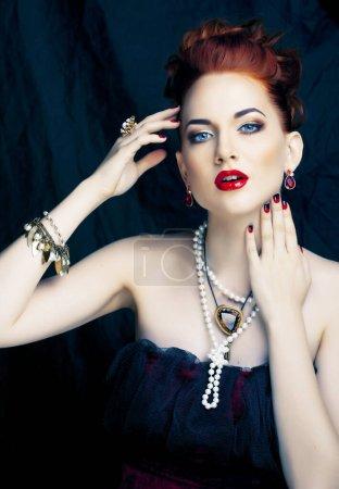 Photo pour Femme de rousse élégante de beauté avec la coiffure et la manucure utilisant le plan rapproché de perle de bijoux - image libre de droit