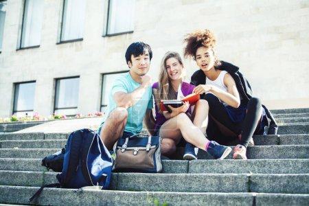Photo pour Groupe mignon d'adolescents à la construction de l'université avec des étreintes de livres, les nations de la diversité de vrais étudiants plan rapproché de style de vie - image libre de droit