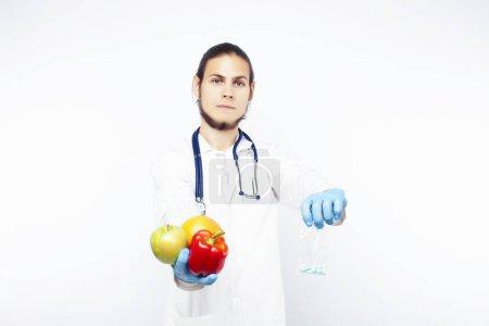 Photo pour Jeune jolie médecin avec stéthoscope tenant des fruits, des légumes et des pilules, seringue, aliments sains Fermeture du concept de soins alimentaires - image libre de droit