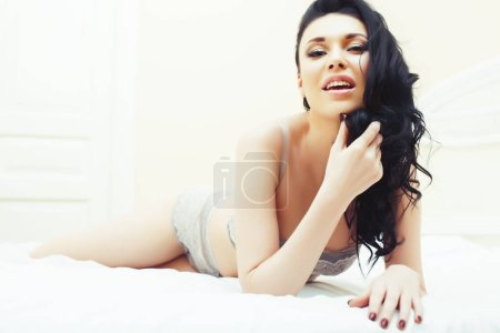Photo for Beautiful brunette woman lying in bed in sensual gray lingerie, looking at camera. Seduction concept in bright luxury room interior closeup - Royalty Free Image