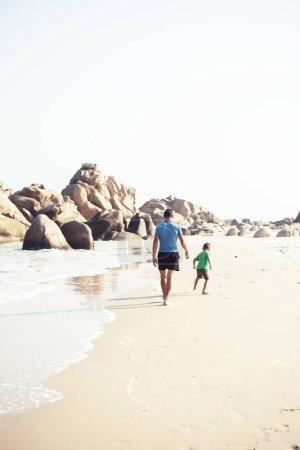 Photo pour Heureux famille sur la plage jouer, père avec fils marche côte de mer, rochers derrière souriant prendre des vacances gros plan - image libre de droit