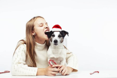 Photo for Pretty young blond girl with her little cute dog wearing Santas red hat at Christmas holiday isolated on white background, lifestyle people concept closeup - Royalty Free Image