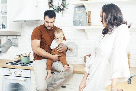 Photo pour Jeune famille avec petit fils mignon sur la cuisine le matin heureux souriant, style de vie gens concept gros plan - image libre de droit