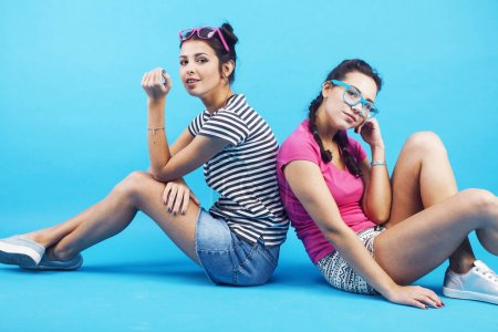 Photo for Lifestyle people concept: two pretty young school teenage girls having fun happy smiling on blue background closeup - Royalty Free Image