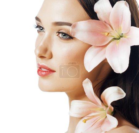 Photo pour Jeune femme séduisante se bouchent avec les mains sur le visage isolé fleur lys spa brune maquillage nude macro - image libre de droit