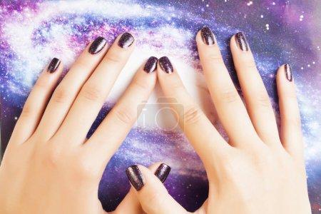 Photo pour Concept manicure stylé : doigts de femme avec ongles violet scintillant sur des ongles comme le cosmos, l'univers en arrière-plan en gros plan - image libre de droit