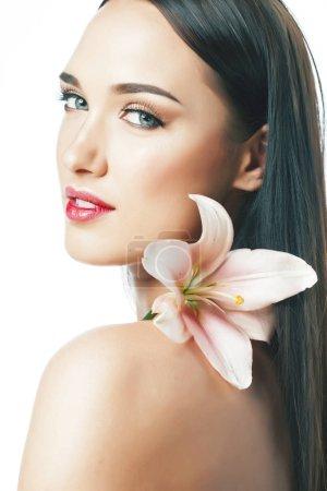 Foto de Joven atractiva dama hasta con las manos en la cara aislado flor lirio morena spa desnudo maquillaje macro primer plano - Imagen libre de derechos