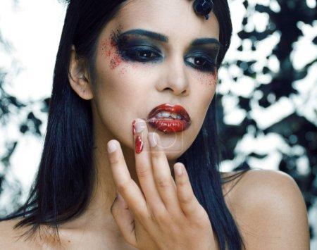 Photo pour Jolie brunette femme avec bijoux rose, noir et rouge, brillant composent kike un closeup vampire lèvres rouges, notion d'halloween - image libre de droit