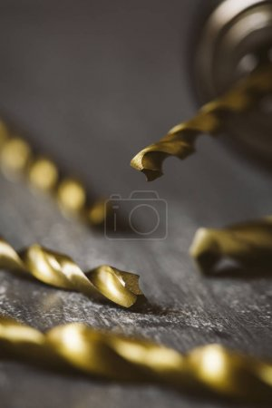 Drill bits of different sizes isolated over wooden background.