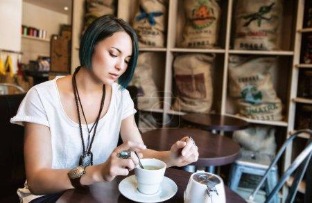 Photo pour Jeune femme devant sa tasse de thé dans un bar - image libre de droit