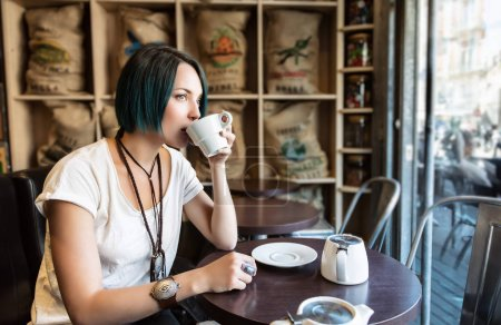 Photo pour Une jeune femme boit une tasse de thé dans un bar - image libre de droit