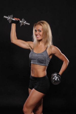 sporty muscular woman working out with dumbbells