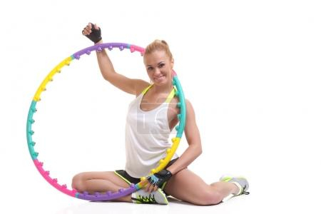 Young sporty woman with hula hoop on a white backg...