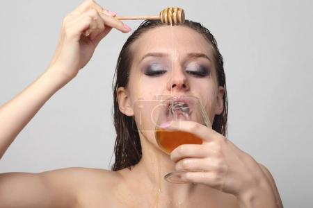 Beautiful woman with honey on her face