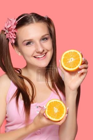 young happy smiling woman holding half of orange