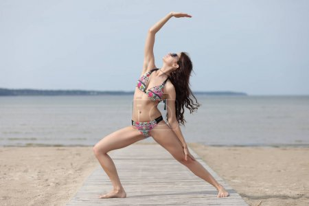 Young, beautiful girl with sexy body meditating on a beach