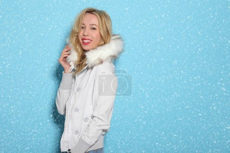 young girl in a white jacket on a blue background