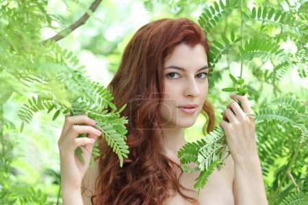 portrait of a young beautiful woman with green leaves