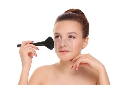 woman applying dry cosmetic powder