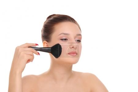 woman applying dry cosmetic powder