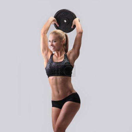 Photo pour Athlétique jeune femme faire de l'exercice avec des poids - image libre de droit