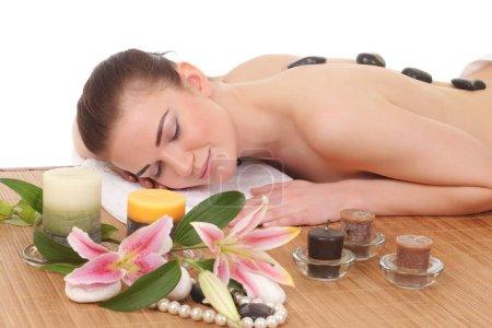 Photo pour Jeune femme portant sur la table de massage avec bougies - image libre de droit