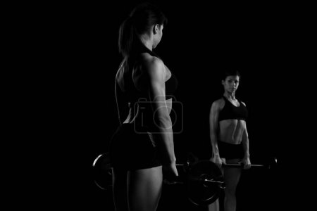 Photo pour Jeune fille forte soulève le barbell sur un fond noir - image libre de droit
