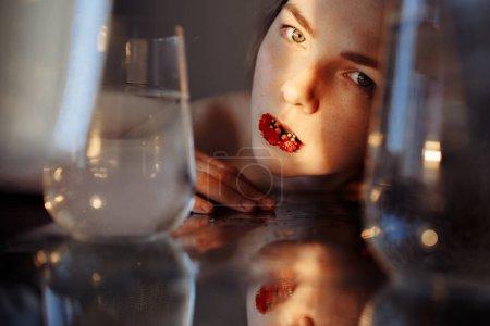 Foto de La cara de las niñas está iluminada por un rayo de luz. El rayo simboliza la esperanza. Hay una flor roja en la boca de las niñas. La cara se refleja en el espejo. Hay contenedores de agua alrededor.. - Imagen libre de derechos