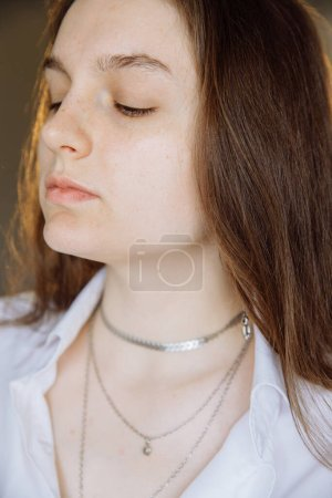 Photo for A beautiful brunette girl looks away with her small nose lifted. The girls eyes are closed. No makeup. A lot of jewelry hangs around her neck. Wearing a white shirt. - Royalty Free Image