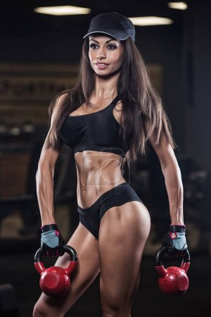 Photo for Fitness woman posing in the gym. Perfect physique athletic young woman with six pack - Royalty Free Image
