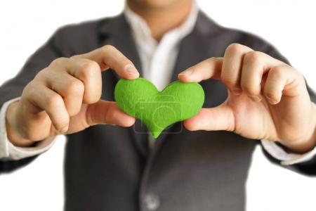 Photo pour Homme d'affaires avec un cœur vert / Entreprise avec responsabilité sociale d'entreprise et préoccupation environnementale - image libre de droit