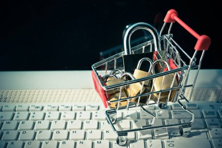 A trolley on computer keyboard with padlocks