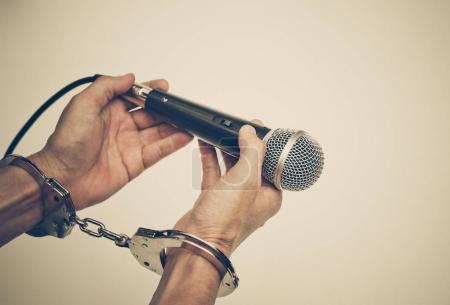 Photo for Hand holding a microphone with handcuffs / Freedom of the press is at risk concept - World press freedom day concept - Royalty Free Image