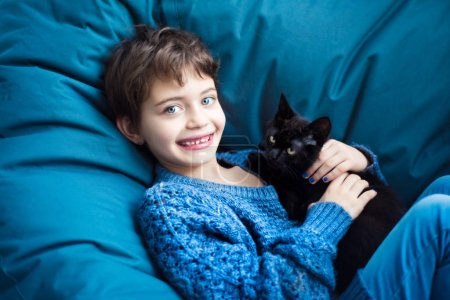 Photo for Portrait of 7 years old smiling girl with short haircut on classic blue chair in classic blue pullover with her friend black kitty with yellow eyes on lap. Friendship between human and animal. - Royalty Free Image