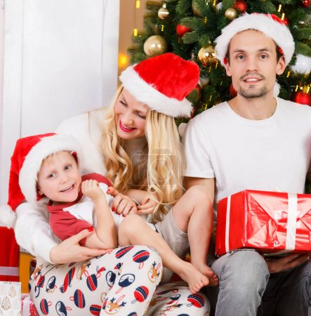 Photo for New Years photo of family with gifts at New Years pine - Royalty Free Image